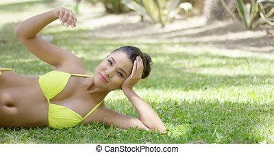 Cute girl lies on grass in exotic park she looking at camera...