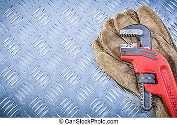 Safety gloves monkey wrench on corrugated metallic sheet...