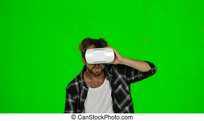 Man walks around the room in a mask of virtual reality. Green screen