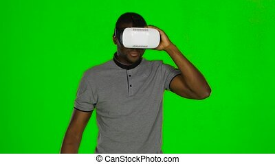 Man wanders around the room and keeps the VR mask by hands....