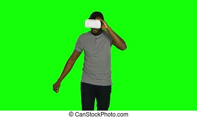 Man in the VR mask something crosses legs in the air. Green...