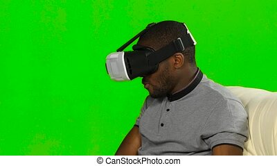 Man in a VR mask watching a movie and eating popcorn. Green screen