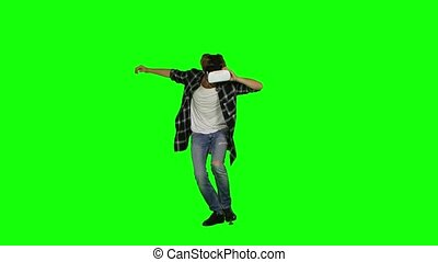 Male wearing a mask of virtual reality on his head. Green...