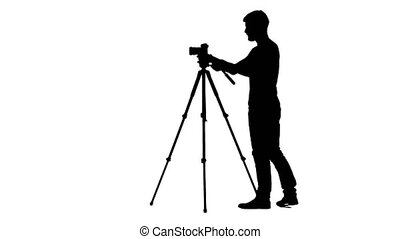 Operator sets the camera to a tripod. Silhouette. White -...