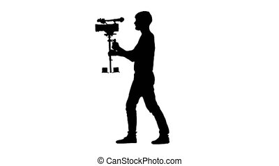 Silhouette of videographer spends filming around itself....