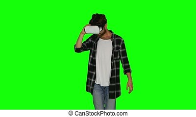 Man in VR mask passes some of virtual obstacles. Green screen