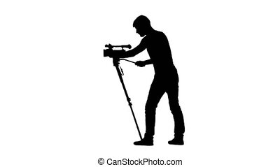 Work of operator with the camera on a tripod. Silhouette