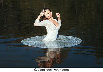 Woman is standing in the lake in the nature - Woman in white...