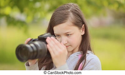 Small girl takes pictures on camera. - Small girl takes...