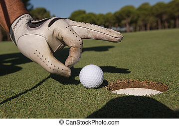 man's hand putting golf ball in hole - close up of man's...