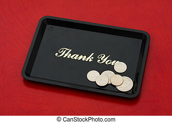 Tip Money - Silver coins on a black tray on a wood...
