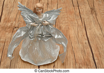 An angel dressed in silver with merry Christmas in gold...