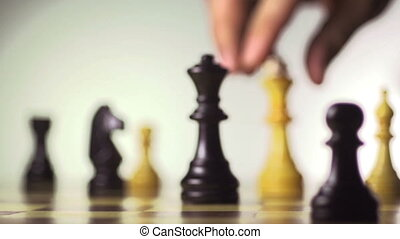 White chess player knocks down the black king with his piece...
