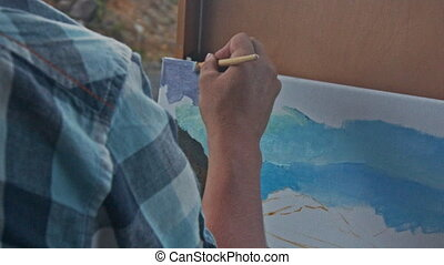Closeup Painter Hand Paints Landscape Picture in Oils -...