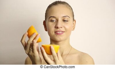 beautiful naked young woman eating an orange. healthy food - strong teeth concept