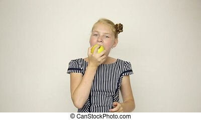 beautiful young girl dressed in a striped dress eating an apple. healthy food - strong teeth concept