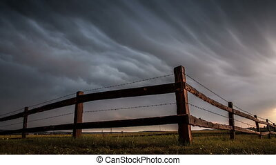 Fence in the field under stormy cloud sky.