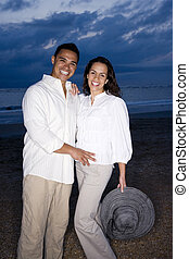 Mid-adult Hispanic couple smiling on beach at dawn - Happy...