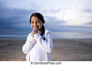 Cute little Hispanic girl smiling on beach at dawn - Cute 9...
