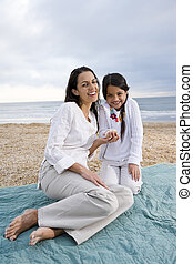 Hispanic mother and girl sitting on blanket at beach - Latin...