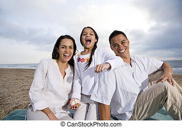 Hispanic family sitting on blanket at beach - Latin American...