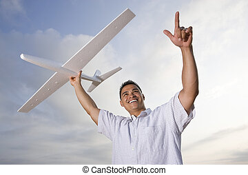 Hispanic man holding model airplane glider over head -...