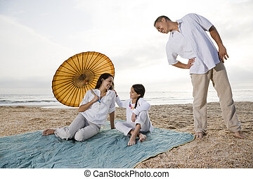 Hispanic family with little girl on beach blanket