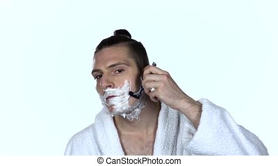 Male shaves face with blade razor. White background. Slow...