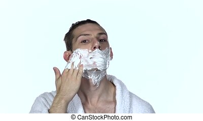 Man gets shaving aid on face. White background. Slow motion