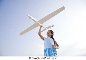 Pretty girl playing with toy glider - Low angle view of...