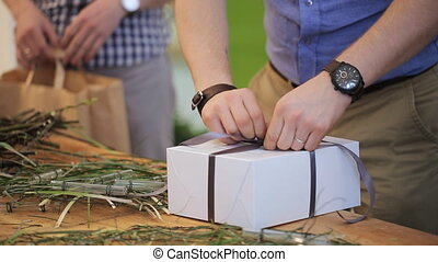 Man is concentrated on untying of bow-knot on box with cake....