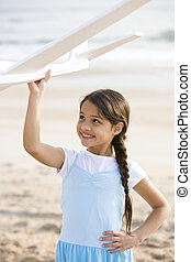 Cute Hispanic girl playing with toy plane on beach