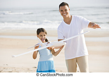 Hispanic girl and dad playing with toy on beach