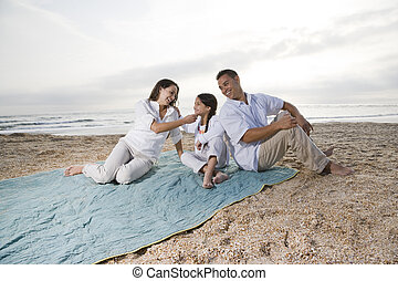 Hispanic family with little girl on beach blanket - Hispanic...