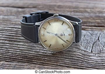 Old broken men wristwatch on wooden board