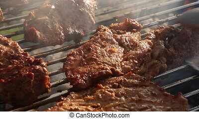 Rotate meat on a barbecue grill, closeup