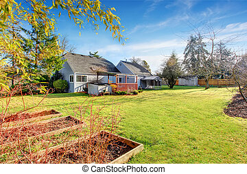 Large back yard with grass, covered deck and grass.