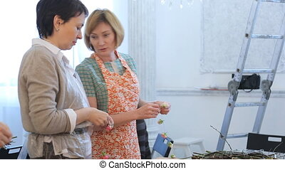 Two women operate with floral elements and talk with each...