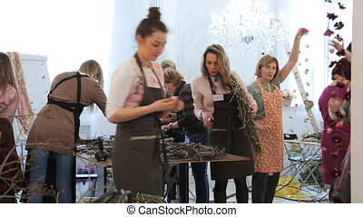 Group of women decorates art studio with floral elements....