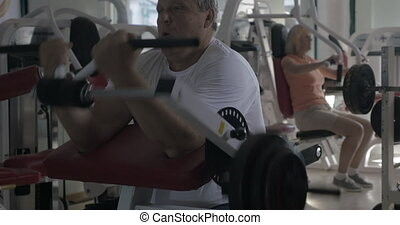 Man working out on biceps in the gym - Senior man exercising...