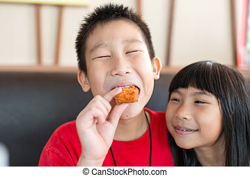 Happy Asian children eating fast food