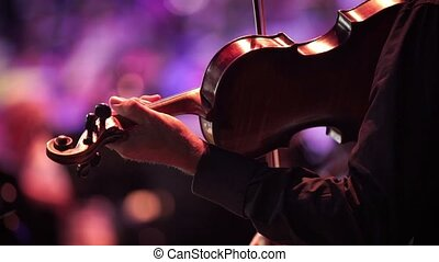 Concert, a musician hand playing the violin, reverse close...