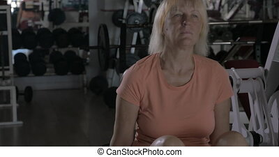 Mature woman training on back extension machine - Senior...