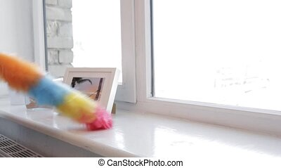 woman with duster cleaning window sill at home - people,...