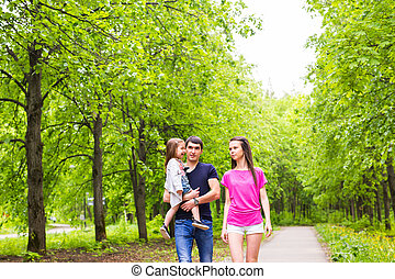 Happy young family walking in green nature. - Happy young...