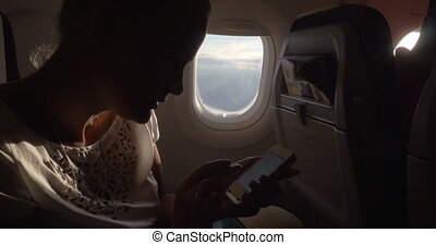 Woman in the plane changing phone settings - Young woman...
