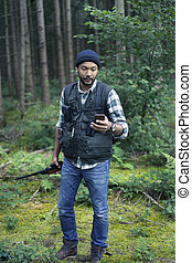 Interracial hunter in the forest using his phone