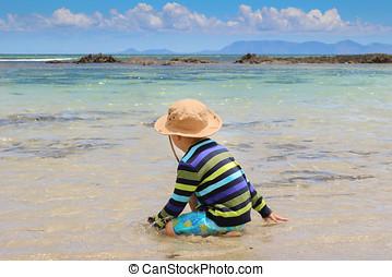 Little boy splashing in shallow sea water