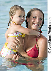 Mother and little girl in swimming pool - Mother and 2 year...