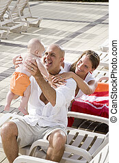 Family vacation, relax on pool deck lounge chairs